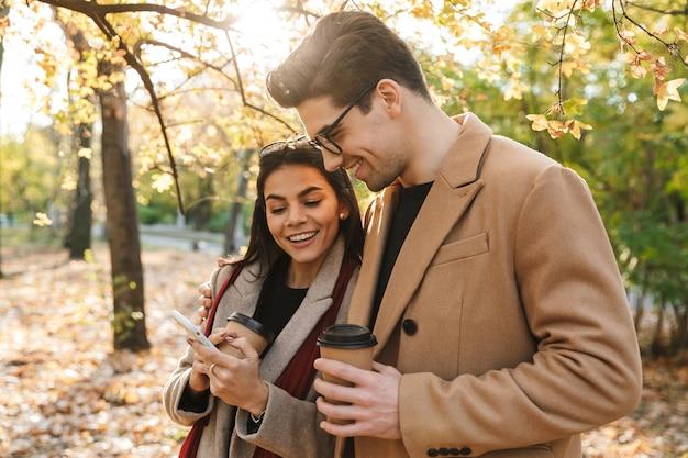 Portret stylowej pary pijącej kawę na wynos z papierowych kubków i patrzącej na smartfona podczas spaceru w jesiennym parku