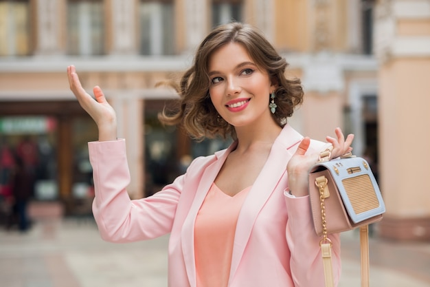 Portret stylowej pięknej kobiety spacerującej w centrum miasta w różowej kurtce trzymającej torebkę, letni trend mody, uśmiechnięty, szczęśliwy, naturalny makijaż, falujące włosy, elegancka dama, romantyczny nastrój