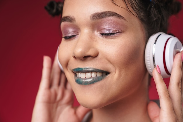 Portret stylowej punkowej dziewczyny z dziwaczną fryzurą i zamkniętymi oczami, uśmiechającej się podczas słuchania muzyki przez słuchawki odizolowane na czerwonej ścianie