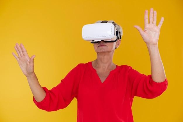 Portret stylowej starszej kobiety korzystającej z gogli wirtualnej rzeczywistości