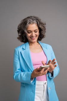 Portret stylowej starszej kobiety trzymającej telefon