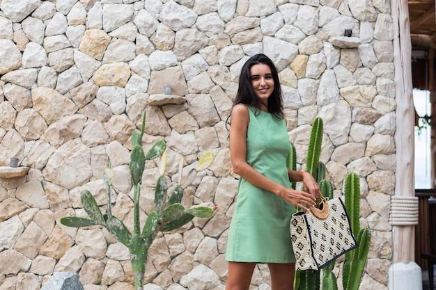 Portret stylowej szczęśliwej ślicznej uśmiechniętej kobiety w eleganckiej letniej zielonej sukience trzymając torbę na sobie słomkowy kapelusz na tle białej kamiennej ściany i kaktusa