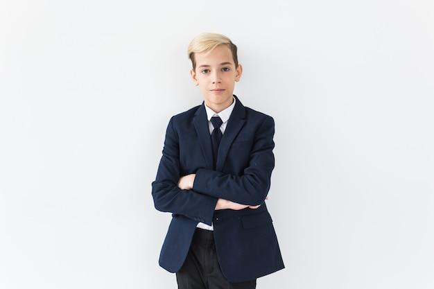 Portret stylowej szkoły nastolatek chłopiec w białej koszuli i kurtce na białej powierzchni.