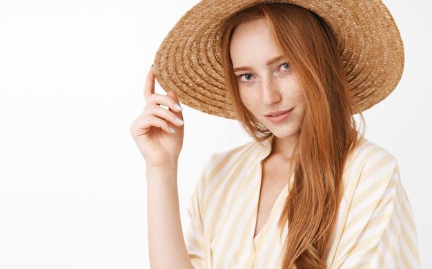 Portret stylowej tajemniczej i zmysłowej pięknej rudowłosej uśmiechniętej zalotnej kobiety z zainteresowaniem i pożądaniem dotykającej słomkowego kapelusza na głowie