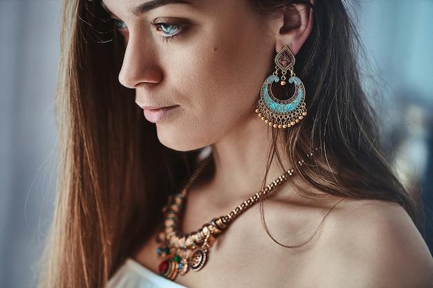 Portret stylowej zmysłowej kobiety boho brunetka o pięknych oczach, ubranych w duże kolczyki i złoty naszyjnik. modny cygański cygański indyjski strój z detalami z biżuterii