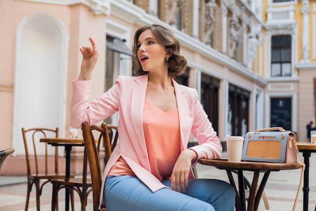 Portret stylowej zmysłowej pani siedzącej przy stole pijącej kawę w różowej kurtce trend w stylu letnim, niebieska torebka, akcesoria, styl uliczny, moda damska