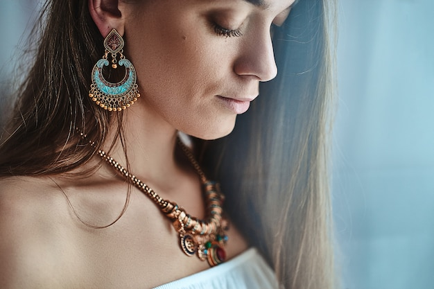 Portret stylowej zmysłowej pięknej brunetki boho szykownej kobiety z dużymi kolczykami i naszyjnikiem. modny cygański cygański indyjski strój z detalami jubilerskimi