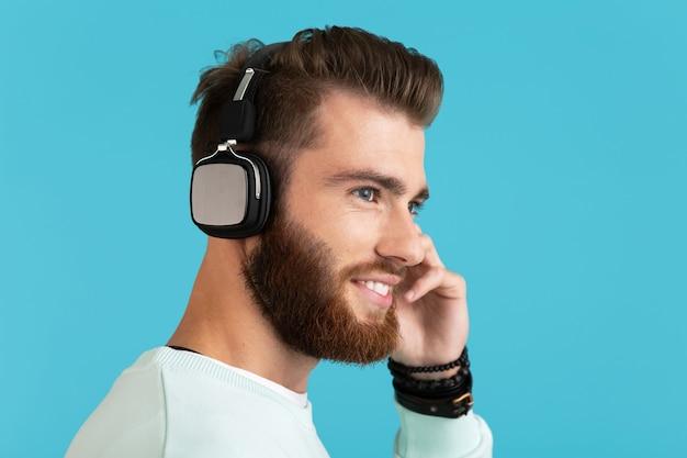Portret stylowy atrakcyjny młody brodaty mężczyzna słuchanie muzyki na słuchawkach bezprzewodowych nowoczesny styl pewny nastrój na białym tle na niebieskim tle