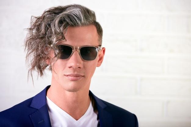 Portret stylowy biznesmen z kręconymi długimi włosami w okulary uśmiecha się do kamery