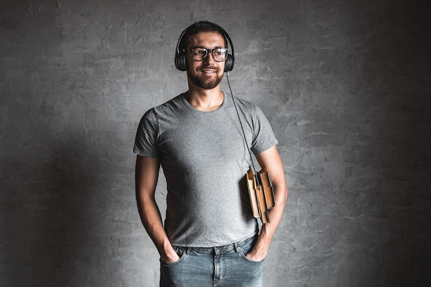 Portret stylowy brodaty mężczyzna ubrany w szary t-shirt dorywczo słuchając książki audio z jego słuchawkami i na szarym tle