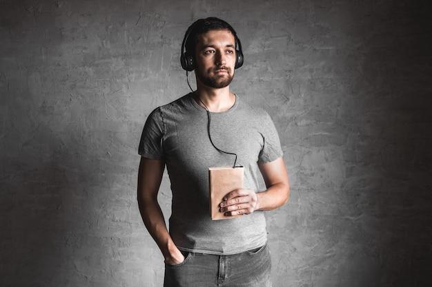 Portret stylowy brodaty mężczyzna ubrany w szary t-shirt dorywczo słuchając książki audio ze słuchawkami i na szaro