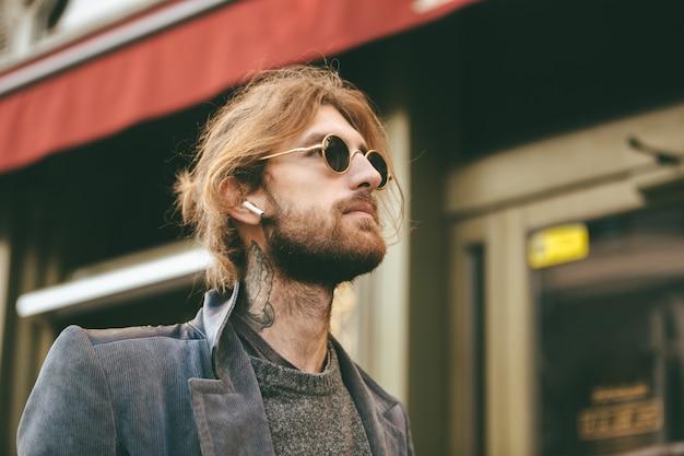 Portret stylowy brodaty mężczyzna w słuchawkach