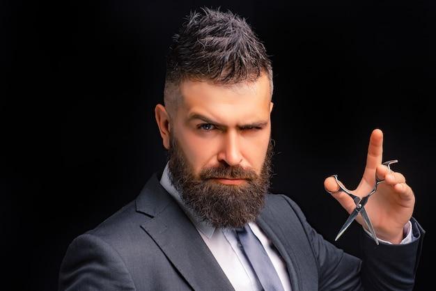 Portret stylowy brodaty mężczyzna z nożyczkami do włosów.