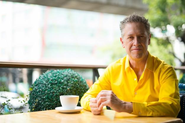 Portret stylowy dojrzały przystojny mężczyzna siedzi w kawiarni
