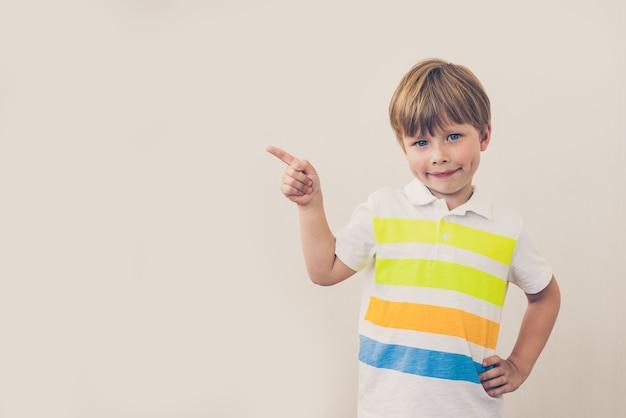 Portret stylowy mały chłopiec z palcem wskazującym w górę
