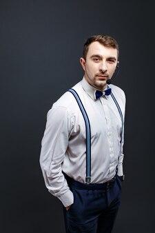 Portret stylowy mężczyzna w szelki i muszka