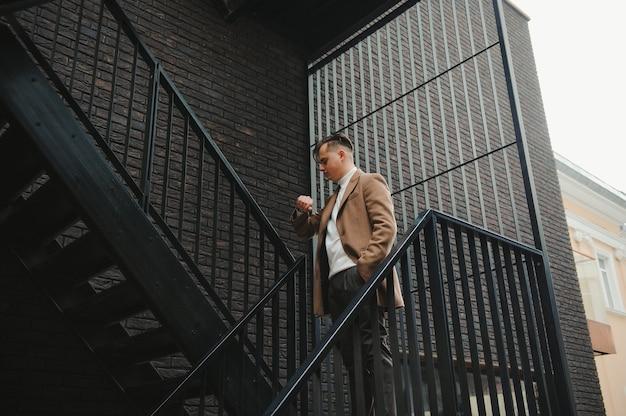 Portret stylowy mężczyzna z brodą ubrany w płaszcz, na zewnątrz
