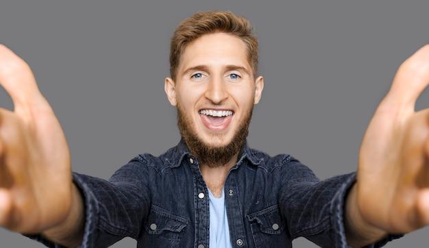 Portret stylowy młody brodaty mężczyzna patrząc na kamery obejmując młody śmiech na białym tle na szarej ścianie studio.