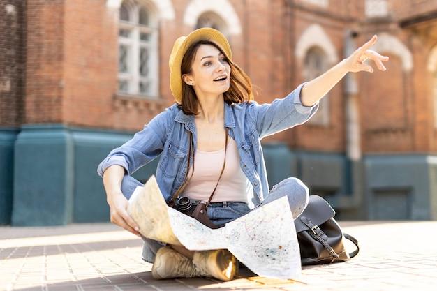 Portret stylowy podróżnik z kapeluszem i mapą