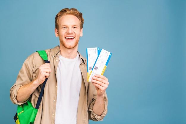 Portret stylowy przystojny brodaty młody mężczyzna. człowiek uśmiechnięty, patrząc na kamery i trzymając bilety.