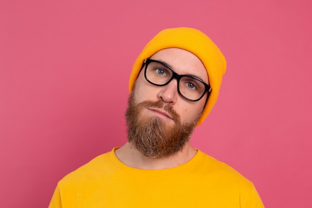 Portret stylowy przystojny europejski brodaty mężczyzna w dorywczo żółtą koszulę i okulary na różowym tle