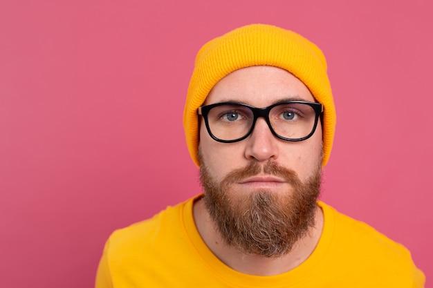 Portret stylowy przystojny europejski brodaty mężczyzna w dorywczo żółtej koszuli i okularach na różowo