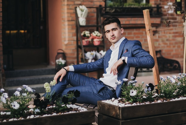 Portret stylowy przystojny młody człowiek siedzi na zewnątrz. biznesmen na sobie kurtkę i zegarek.