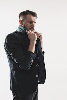 Portret stylowy przystojny młody człowiek stojący w studio przed białym. mężczyzna w kurtce