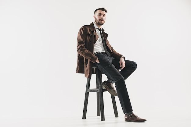 Portret stylowy przystojny młody mężczyzna siedzi w studio przed białym. mężczyzna w kurtce
