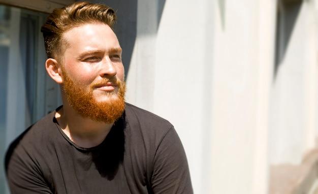 Portret stylowy rudy brodaty młody człowiek.