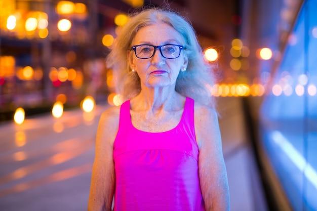 Portret stylowy starszy kobieta na zewnątrz w nocy
