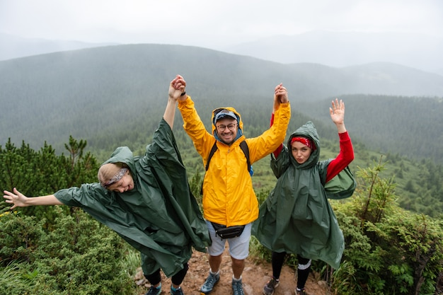 Portret stylu życia podekscytowana grupa śmiejących się podróżników w płaszczach przeciwdeszczowych wysoko w górach.