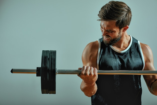 Portret super fit muskularny młody człowiek, ćwicząc w siłowni ze sztangą na szarym tle