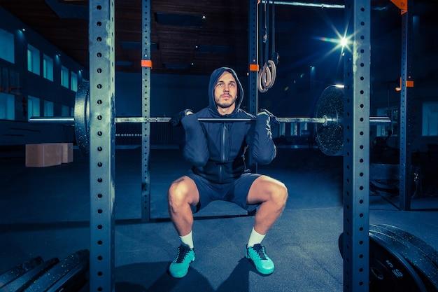 Portret super fit muskularny młody człowiek, poćwiczyć w siłowni ze sztangą