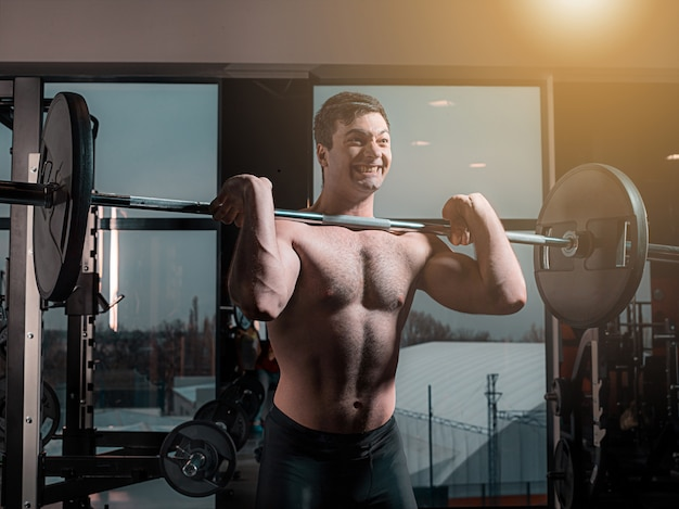 Portret super pasuje mięśni młody człowiek, poćwiczyć w siłowni ze sztangą