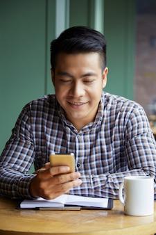 Portret surfuje sieć na smartfonie w coffeeshopie azjatycki uczeń