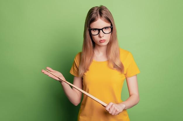 Portret surowej poważnej nauczycielki, pani trzyma wskaźnik, nosi okulary, żółty t-shirt, wygląda na aparat marszczący brwi