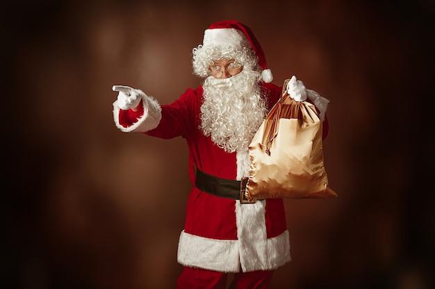 Portret świętego mikołaja w czerwonym stroju z torbą na prezent