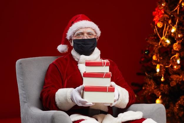 Portret świętego mikołaja w masce ochronnej siedzi na fotelu z pudełkami na prezenty przygotowuje prezenty dla dzieci na boże narodzenie