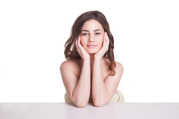 Portret świeżej i pięknej brunetki ubranej w biały ręcznik