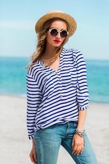 Portret świeżej młodej kobiety w fajne okulary przeciwsłoneczne i słomkowy kapelusz, pozowanie na słonecznej tropikalnej plaży