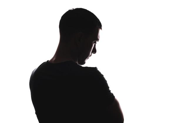 Portret sylwetka mężczyzny rasy kaukaskiej zamyślony patrząc, od tyłu patrząc w dół, na białym tle