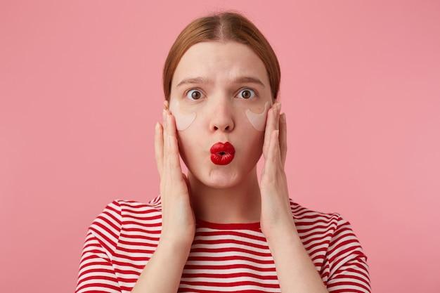 Portret sympatycznej młodej zdumionej rudowłosej pani w czerwonej koszulce w paski, z czerwonymi ustami i łatami pod oczami, zdziwiona spojrzeniem i wstaniem.