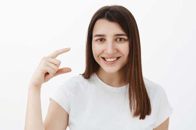 Portret sympatycznej, przyjaznej i optymistycznej młodej brunetki w białej koszulce, uśmiechnięta usatysfakcjonowana kształtowaniem małego lub malutkiego przedmiotu w dłoni, opowiadająca o małym produkcie na szarej ścianie