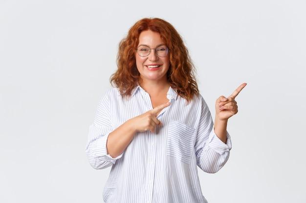 Portret sympatycznej uśmiechniętej kobiety w średnim wieku o rudych włosach, w okularach i bluzce z reklamą, klient firmy poleca produkt lub usługę, wskazując w prawo.
