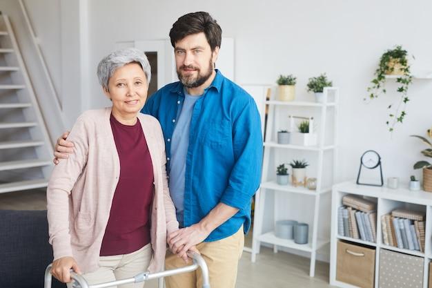 Portret syna stojącego wraz ze swoją starszą matką w pokoju i uśmiechnięte