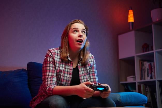Portret szalonego, figlarnego gracza, dziewczyny bawiącej się graniem w gry wideo w pomieszczeniu, siedząc na sofie, trzymając w rękach kontroler konsoli. odpoczywając w domu, miłego weekendu