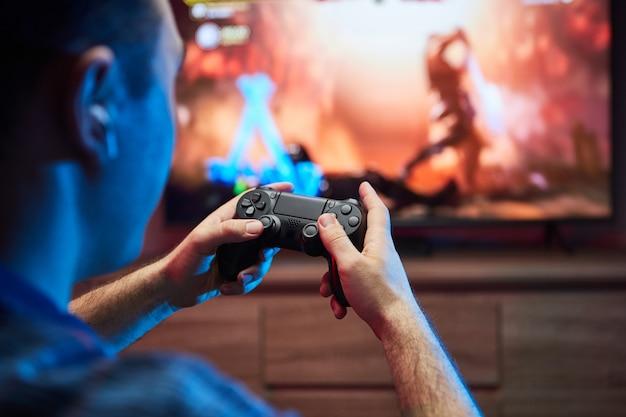 Portret szalonego figlarnego gracza, grającego w gry wideo