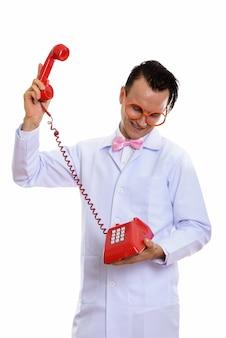 Portret szalonego młodego lekarza przy użyciu starego telefonu