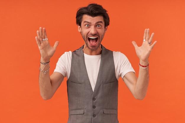 Portret szalonego, wściekłego młodzieńca z zarostem i uniesionymi rękami wygląda szalenie i krzyczy